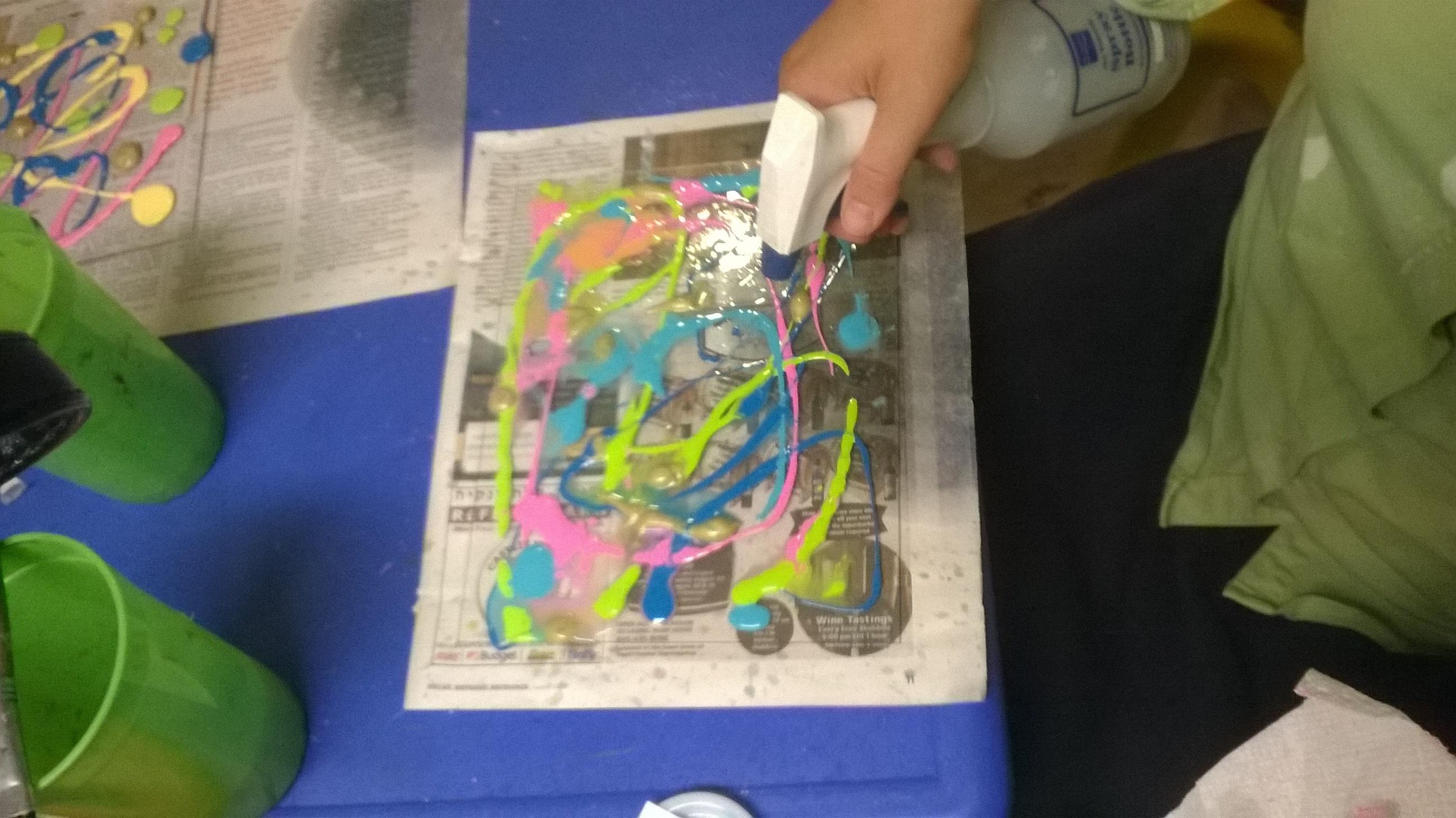 spritzing dimensioanl paint onto plexiglass