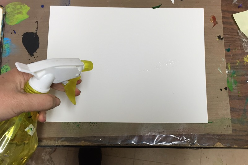 spraying watercolor paper with water